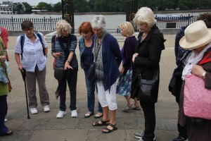 Greenwich - a guide tells the history of a pavement inscription