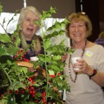 Margaret Gaines and Trish Mather hiding behind the festive decorations